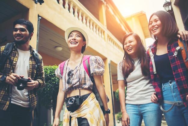 都市の通りで歩いて楽しい幸せな若い友人のグループ。友情旅行のコンセプト。
