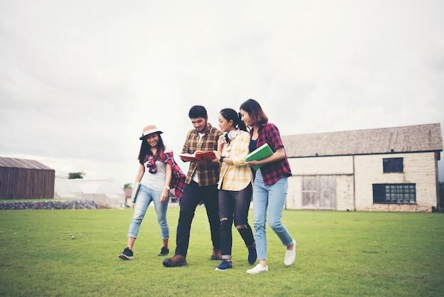 クラス後に公園を歩く学生のグループ。一緒に話を楽しんでください。
