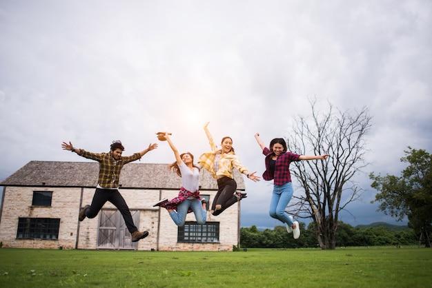 公園でジャンプする十代の学生の幸せなグループ