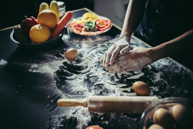 女性は木製の上にピザを作るために生地を混練する。料理のコンセプト。