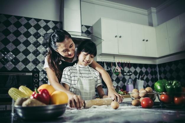 キッチンのローリングピンを使って生地を平らにするエプロンのかわいい女の子と彼女のお母さん