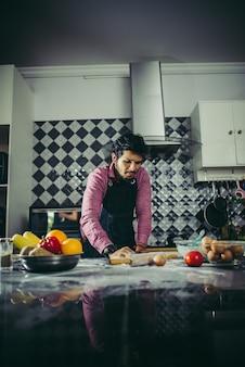 自家製のピザ生地を台所で混練する男。料理のコンセプト。