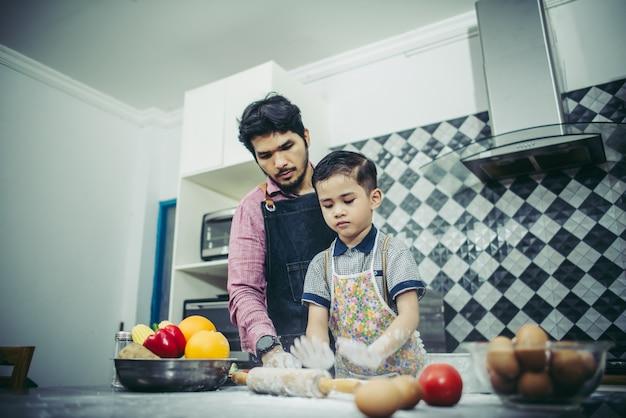 お父さんは自宅でキッチンで調理する方法を息子に教えます。家族のコンセプト。