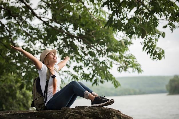 バックパックで座っている若い幸せな女性はハイキングの後で自然を楽しむ。