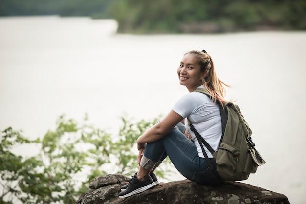 Молодая женщина с рюкзак сидеть пользуются с лесом. концепция путешествия.