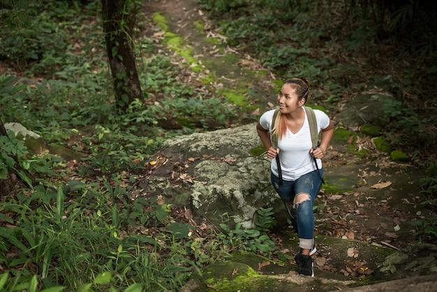 自然に幸せな森を歩いている若いバックパッカーを閉じます。旅行のコンセプト。