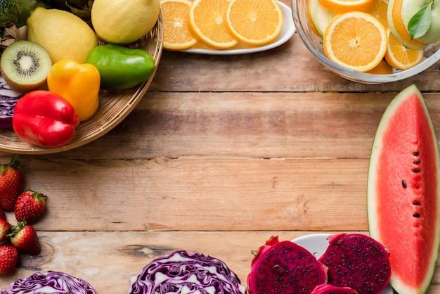 木製の背景に野菜と様々な果物