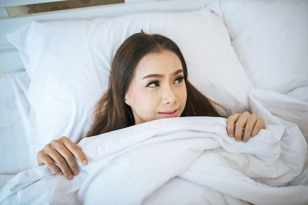 Красивая женщина просыпается в своей постели, ленив утром