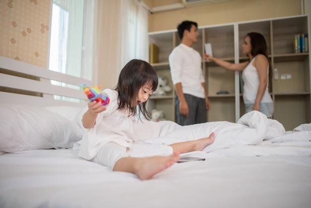 Маленькая девочка сидит с родителями на кровати, глядя серьезной