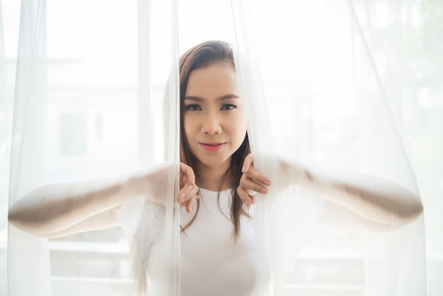 Молодая женщина, стоящая просыпаться в спальне