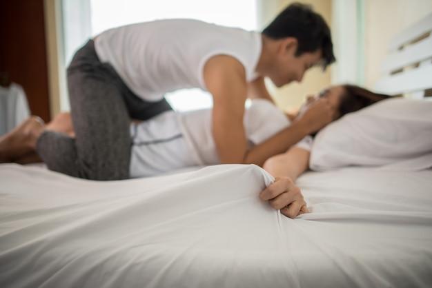 官能的な前景を楽しむベッドのロマンチックな幸せなカップル。