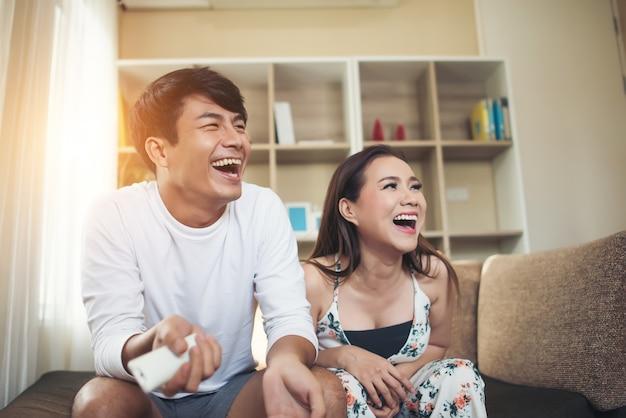 リビングルームでリラックスしてテレビを見ている幸せな若いカップル
