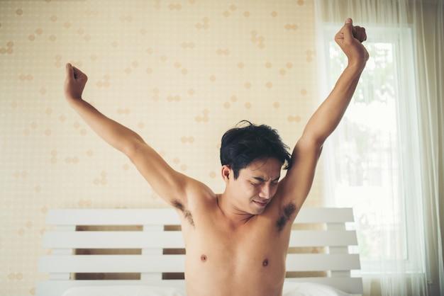 ハンサムな男が目を覚まし、朝のベンで手を上げる