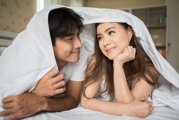 ベッドで毛布の下で遊ぶ甘いカップル