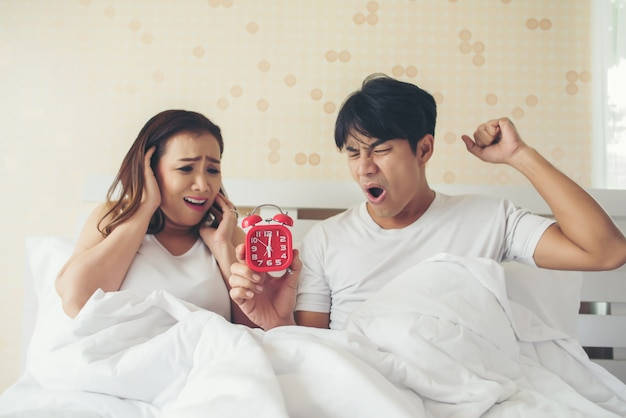 ベッドで朝早く起きるのに苦労しているカップル