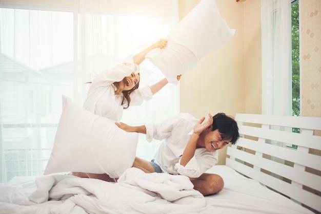 幸せな若いカップルはベッドで楽しいです