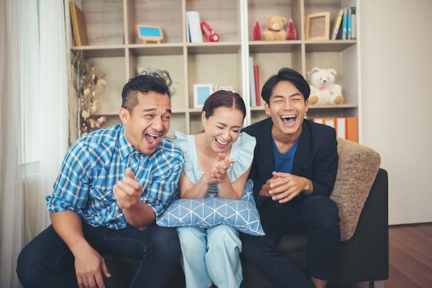 Три счастливых друзей говорят и смеются после просмотра анекдота
