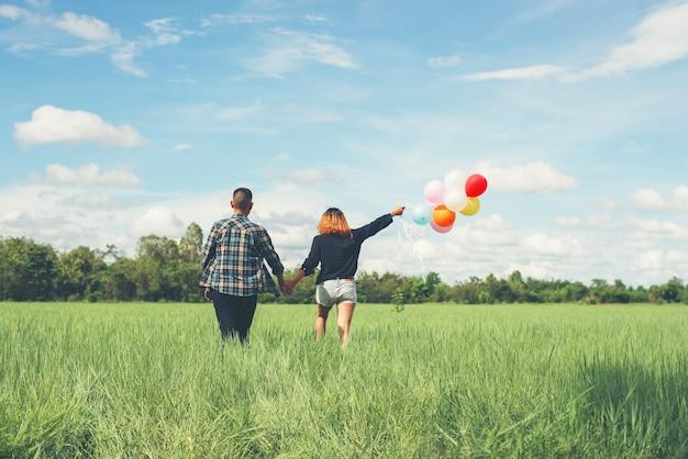 色付きの風船を持って歩くカップル