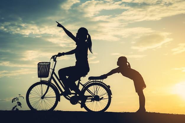 彼女の娘と自転車を持つ母のシルエット