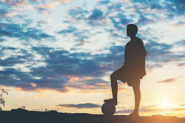 子供たちのシルエットがサッカーをする