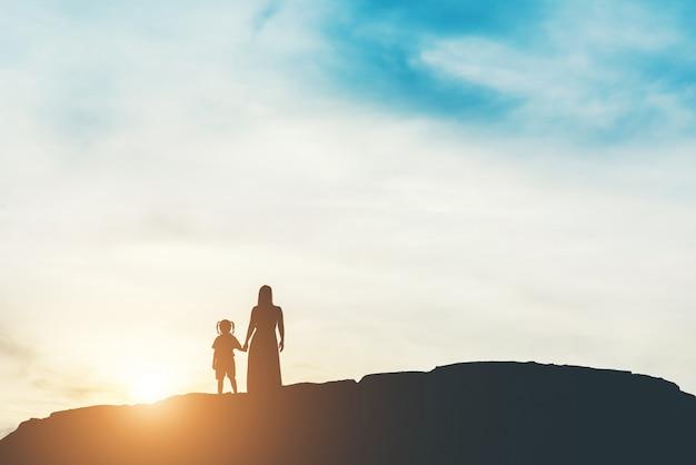 立っていると日没の彼女の娘を持つ母のシルエット