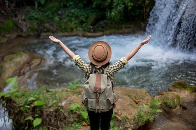 女性観光客は幸せで、滝でリフレッシュします。
