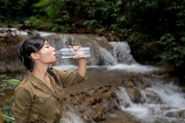 女性は森の中で新鮮な水を飲んでハイキングしています