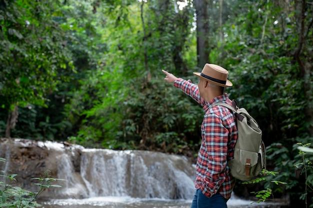 男性の観光客は幸せで滝でリフレッシュします。