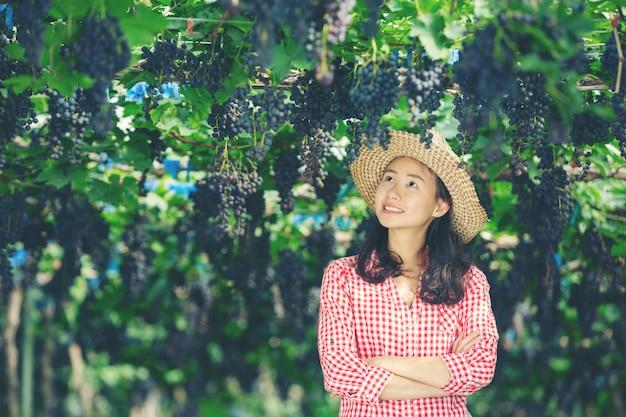 笑顔で収穫を楽しむブドウ畑の農家。