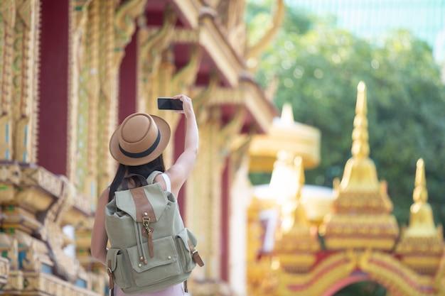 女性観光客が携帯電話で写真を撮る