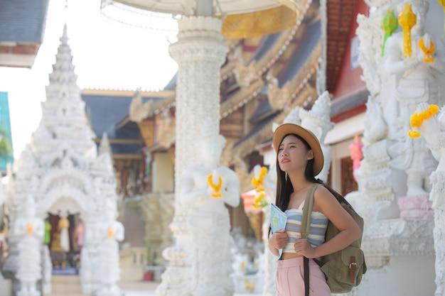 女性観光客は場所を見つけるために地図を持っています。