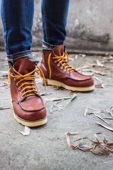 Мужская нога с коричневыми кожаными туфлями и джинсами
