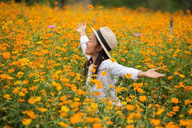 黄色の花農場でアジアの女性