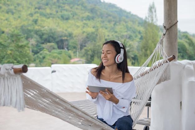 タブレットで音楽を聴くのハンモックに横になっている女性