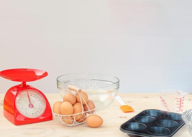 白い木製のテーブルの上にケーキを作るための準備の原料
