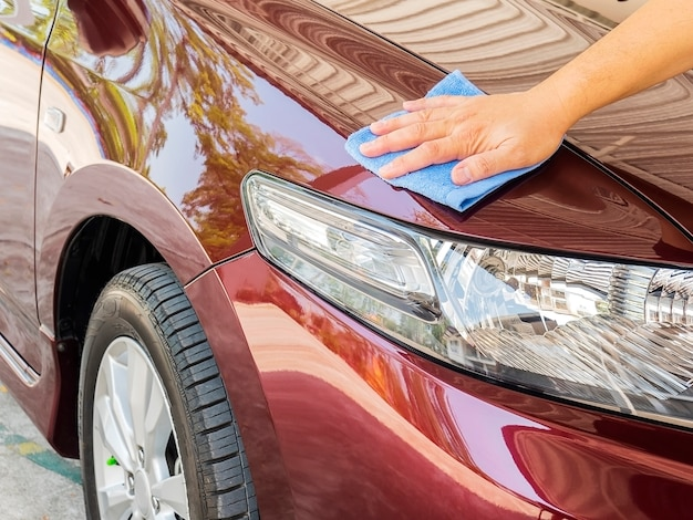 Мужская рука чистит и вощет машину