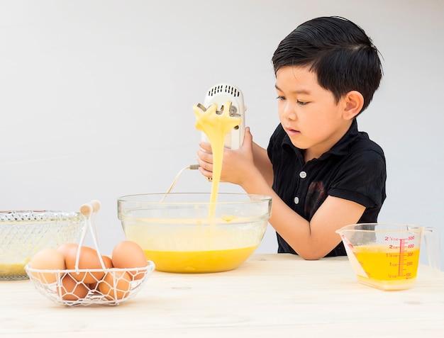 男の子がケーキを作っています。写真は彼の顔に焦点を当てています。