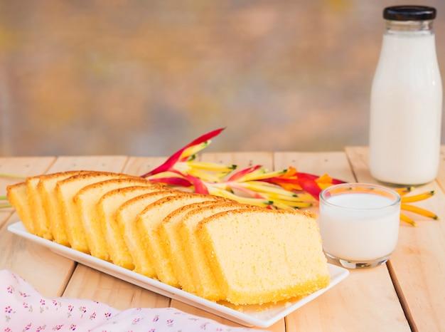 バターケーキと白い木製のテーブルの上のミルクのガラスの瓶