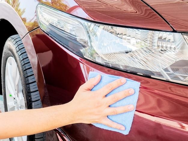 男の手は車を掃除してワックスをかけている