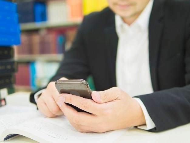 ビジネスマンは彼のオフィスで働いている間携帯電話を使用しています。