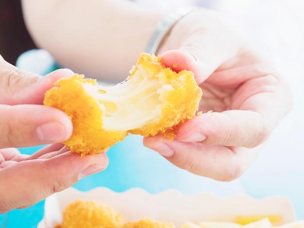 手は青いテーブル背景に食べられるように準備ができてストレッチチーズボールを保持しています。