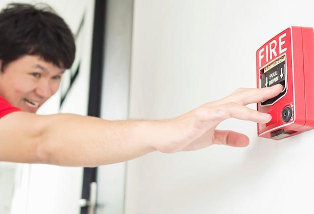 男は火災警報手の駅を押すために彼の手に達しています。