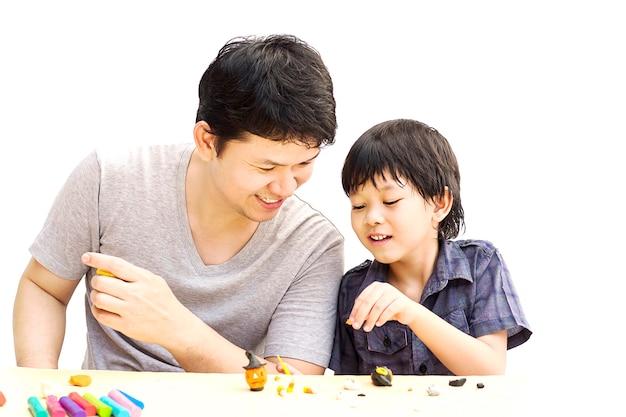 父は彼の息子とハロウィーンクレイを白い背景の上で遊んでいます。