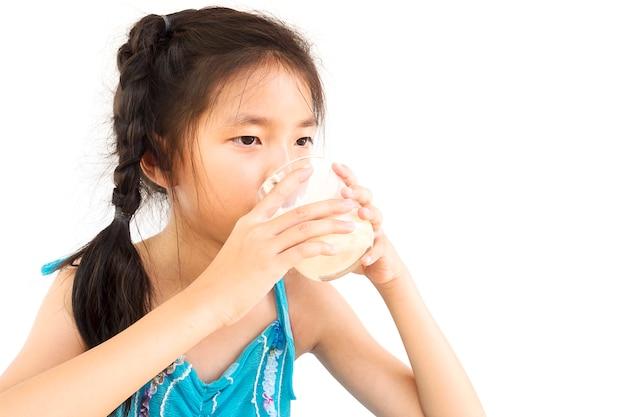 アジアの女の子は白い背景の上にミルクのガラスを飲んでいます