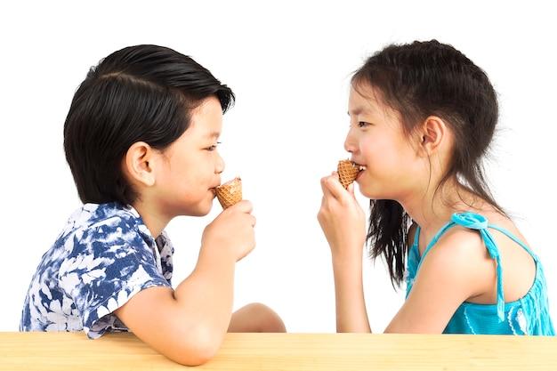アジアの子供たちはアイスクリームを食べています