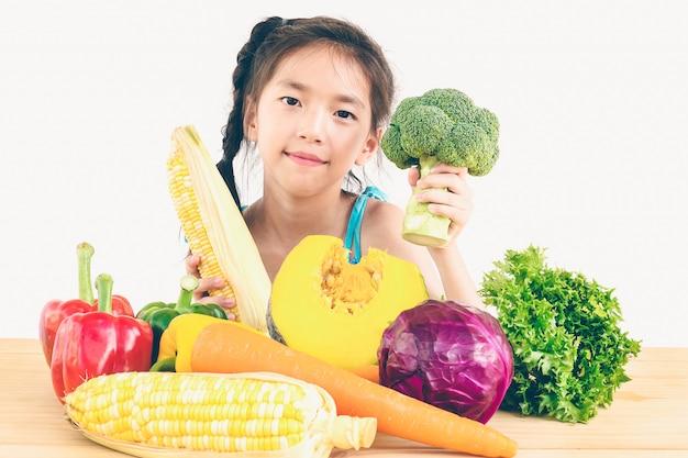 アジアの素敵な女の子を示す新鮮なカラフルな野菜の表現を楽しむ