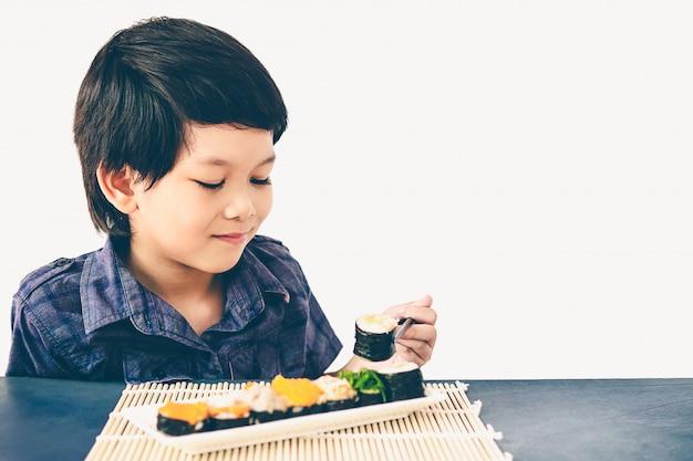 アジアの素敵な男の子のビンテージスタイルの写真は寿司を食べています。