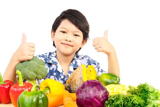 アジアの健康的な少年の様々な新鮮なカラフルな野菜と幸せな表情を示す