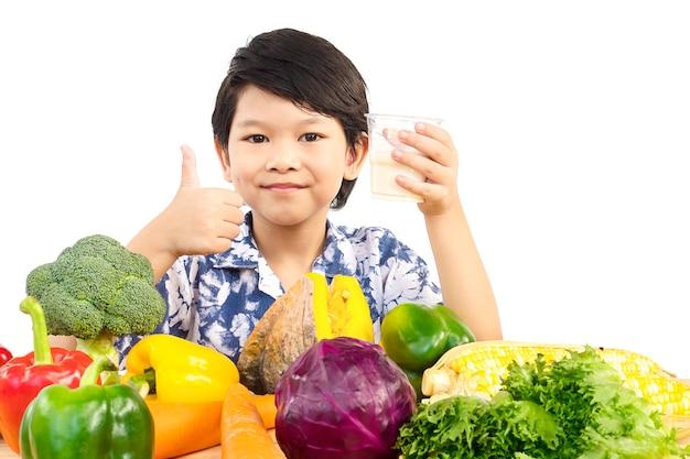 牛乳と様々な新鮮な野菜のグラスと幸せな表情を示すアジアの健康的な少年