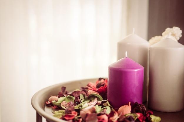 Винтажное фото декоративных свечей и душистых сухих цветочных лепестков в комнате